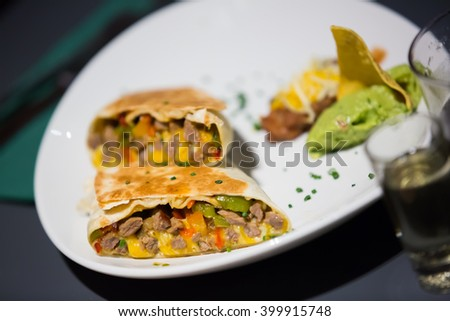 Mexican burrito with meat and beans filling served with guacamole  - stock photo