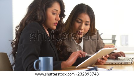 Mexican businesswoman sharing findings on tablet with Japanese colleague - stock photo