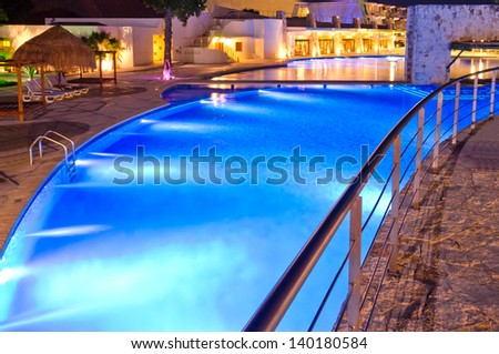 Mexican-caribbean resort swimming pool at night.
