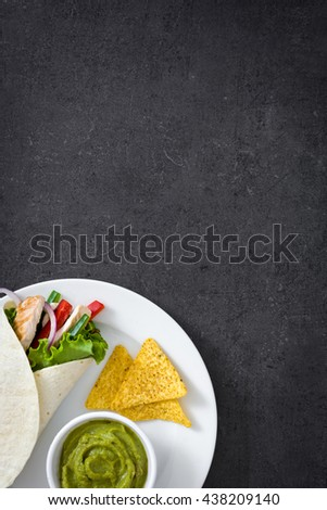 Mexican chicken fajitas with peppers lettuce and onion, nachos and guacamole on slate background   - stock photo
