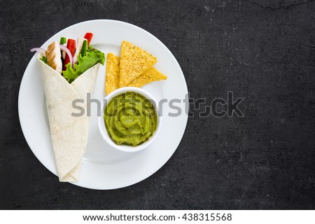 Mexican chicken fajitas with peppers lettuce and onion on a plate and slate background   - stock photo