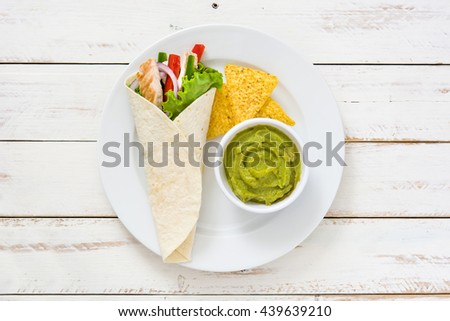 Mexican chicken fajitas with peppers lettuce and onion on a plate and white wooden background   - stock photo