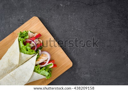Mexican chicken fajitas with peppers lettuce and onion on slate background   - stock photo