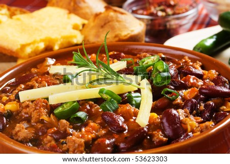 Mexican chili con carne garnished with spring onion and hot peppers - stock photo