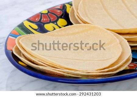 Mexican corn tortillas on retro vintage carrara marble in beautiful talavera plate, perfect for all your Mexican and tex-mex recipes.