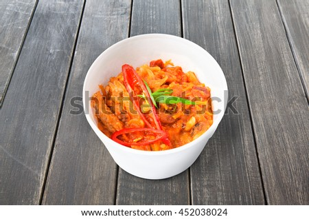 Mexican cuisine food delivery - chili con carne in white plastic plate closeup at rustic gray wood background - stock photo