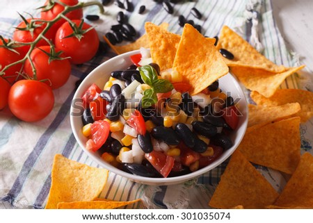 Mexican cuisine: tasty salsa with beans in a bowl and corn chips nachos on the table close-up. horizontal