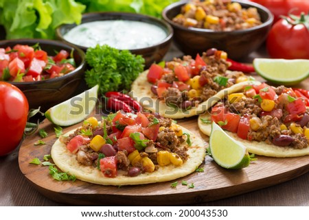 Mexican cuisine - tortillas with chili con carne and tomato salsa on wooden board, horizontal - stock photo