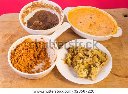 Mexican dinner leftovers on wooden cutting board - beans, rice, chile con queso and chicken enchiladas. - stock photo