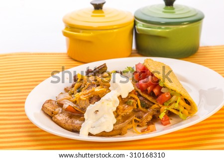 "Mexican Dinner with Tex-Mex Chicken dish ""Pollo Elegante"" and crunchy taco with strong back lighting in colorful Mexican Restaurant Setting. - stock photo"