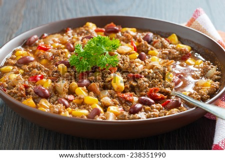 Mexican dish chili con carne in a brown pottery plate, close-up, horizontal