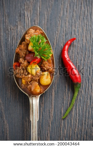 Mexican dish chili con carne in a spoon on a wooden background, concept photo, top view, vertical - stock photo