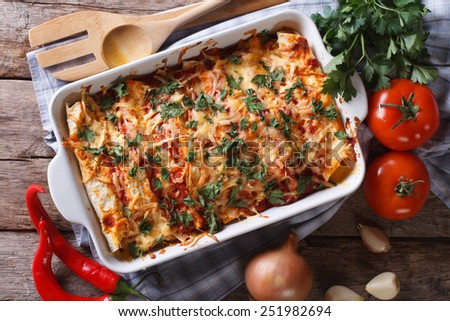 Mexican enchilada in a baking dish with the ingredients on the table close-up. horizontal view from above  - stock photo