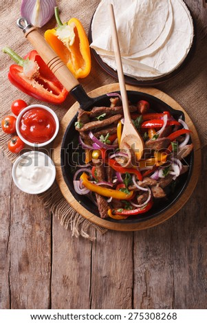 Mexican fajitas on a table in a rustic style. Vertical close-up view from above