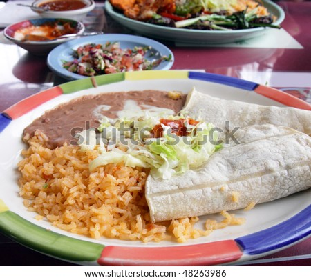 Mexican feast of soft tacos, rice, and beans - stock photo
