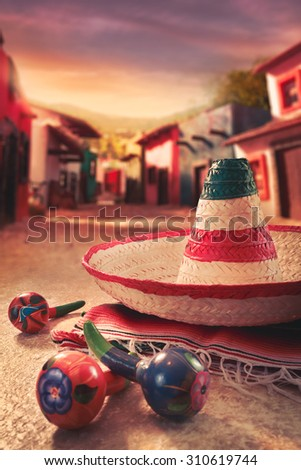 """Mexican fiesta background with a hat """"sombrero"""" and """"maracas"""" in a mexican town - stock photo"""