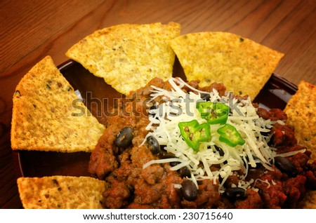 Mexican food: chili with meat served with nachos on wooden background - stock photo