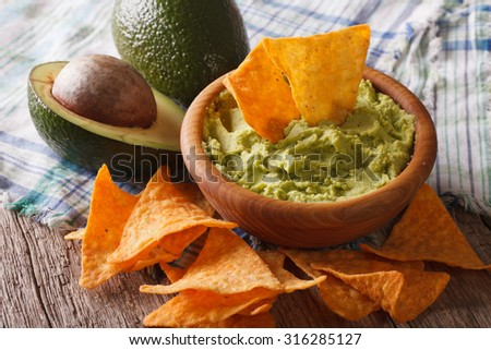 Mexican food: guacamole sauce in a wooden bowl, nachos and avocado close-up. Horizontal
