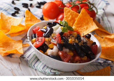 Mexican Food: salsa with black beans in a bowl and corn chips nachos closeup. horizontal  - stock photo