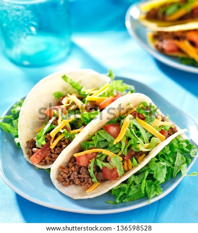 Mexican food - Soft shell tacos with beef, cheese, lettuce and tomatoes - stock photo