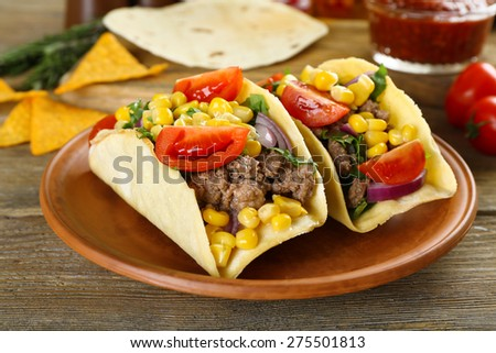 Mexican food Taco in clay plate on wooden table, closeup