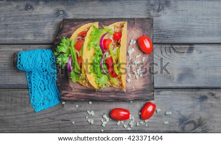 Mexican food tacos, peppers, cherry tomatoes, grated cheese, minced meat in a corn tortilla on board with blue lace, gray wooden background, top view - stock photo