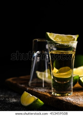 Mexican Gold Tequila with lime and salt on wooden table, selective focus. Shallow depth of field.