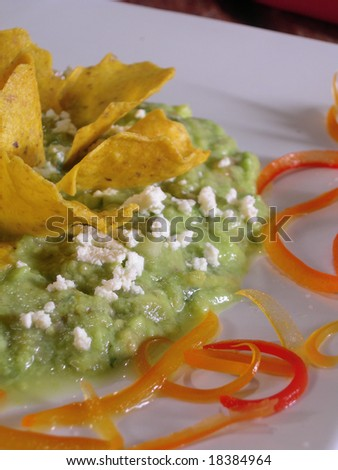 Mexican guacamole with nachos, in a mexican restaurant. - stock photo