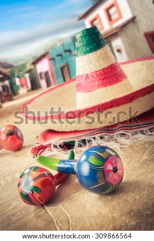 """Mexican hat """"sombrero"""" with """"maracas"""" on a """"serape"""" in a mexican town - stock photo"""