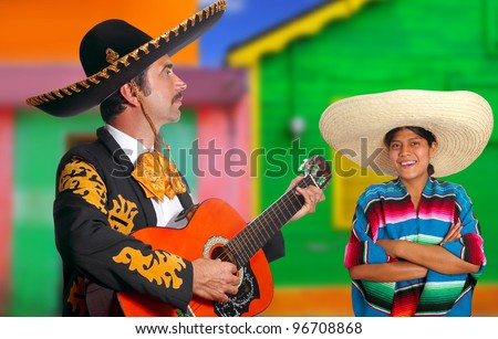 Mexican mariachi charro man singing a song to a poncho Mexico girl - stock photo