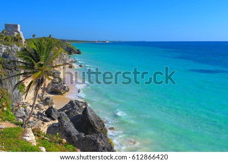 Mexican mayan temple, pyramid in Tulum made from the limestone, close to the beautiful tropical caribbean sea. White fine sandy beach with palm trees, azure water.