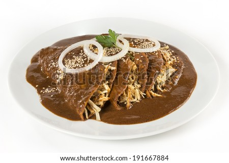 Mexican 'Mole' Enchiladas isolated This enchiladas where made by a Mexican chef using exquisite 'mole' sauce from the state of Puebla. They are served only with onion rings and sesame seeds.  - stock photo
