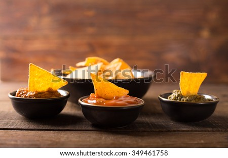 Mexican nacho chips and various sauces in bowl on wooden background - stock photo