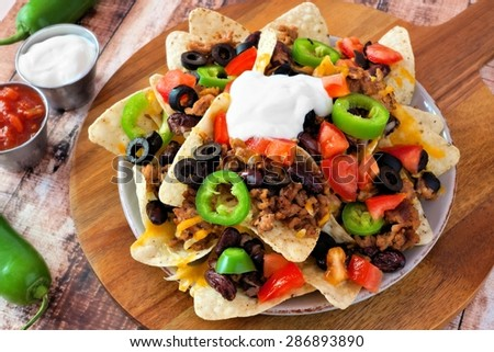 Mexican nacho chips topped with sour cream, ground meat, jalapenos, tomatoes, beans and melted cheese on a wooden paddle board - stock photo