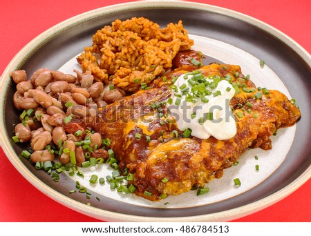 Mexican Plate with beef enchiladas; Spanish rice and borracho beans against red background.  Garnished with green scallions.