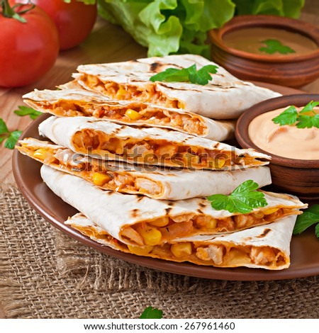 Mexican Quesadilla sliced with vegetables and sauces on the table - stock photo
