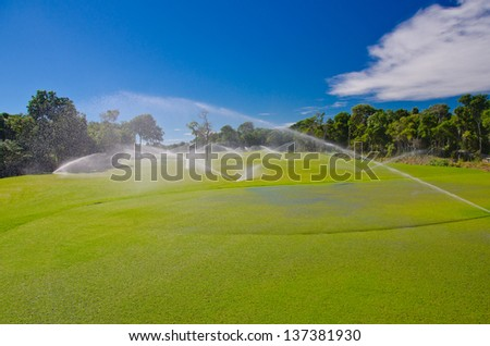 Mexican resort golf course gets irrigated. Golf field, course sprinkling. - stock photo
