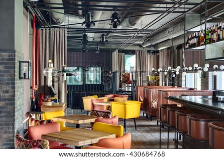 Mexican restaurant in a loft style. On the left there are wooden tables with multi-colored chairs and a wooden stand with a monitor and dishes. On the right there is a black bar rack with brown chairs - stock photo