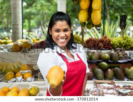 Mexican saleswoman offering fruits on a farmers market - stock photo