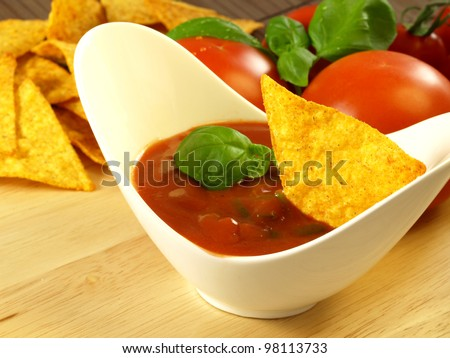 Mexican salsa sauce with nachos and tomatoes in a background.
