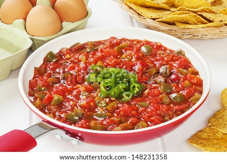 Mexican sauce salsa ranchera, made with onions, garlic, chilli, toasted cumin seeds, Mexican oregano, green peppers and tomatoes. Delicious with fried eggs and corn chips. - stock photo