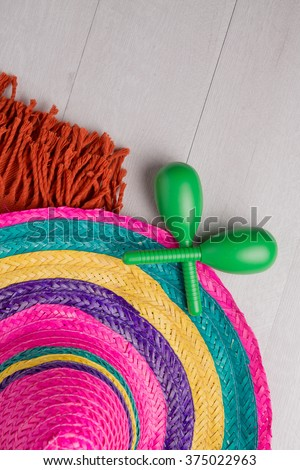Mexican sombrero, blanket and pair of maracas on wood background.