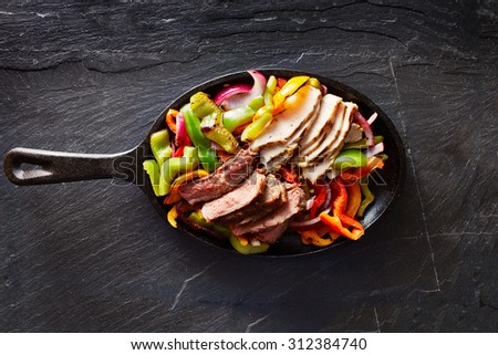 mexican steak and chicken fajitas in cast iron skillet shot top down - stock photo