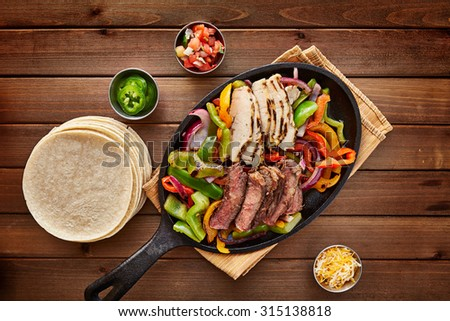 mexican steak and chicken fajitas in cast iron skillet shot top down with corn tortillas - stock photo