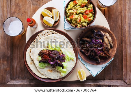 mexican street tacos and fajitas with mushrooms, onions, guacamole. and beer. on a wooden table - stock photo