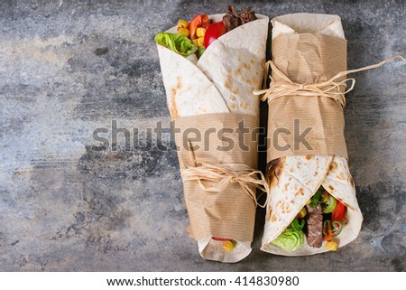 Mexican style dinner. Two papered tortillas with beef and vegetables over old textured tin background. Flat lay with copy space - stock photo