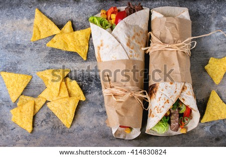 Mexican style dinner. Two papered tortillas with beef and vegetables served with nachos chips over old textured tin background. Flat lay