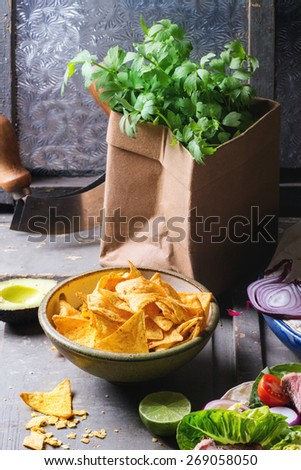 Mexican style dinner with tortilla, herbs, corn chips nachos  and guakomole, served over gray wooden table - stock photo