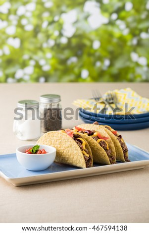 Mexican tacos with beef, cheddar cheese, tomato, beans and salsa dips