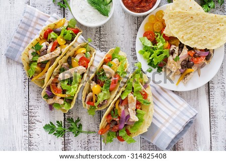 Mexican tacos with chicken, bell peppers, black beans and fresh vegetables. Top view - stock photo